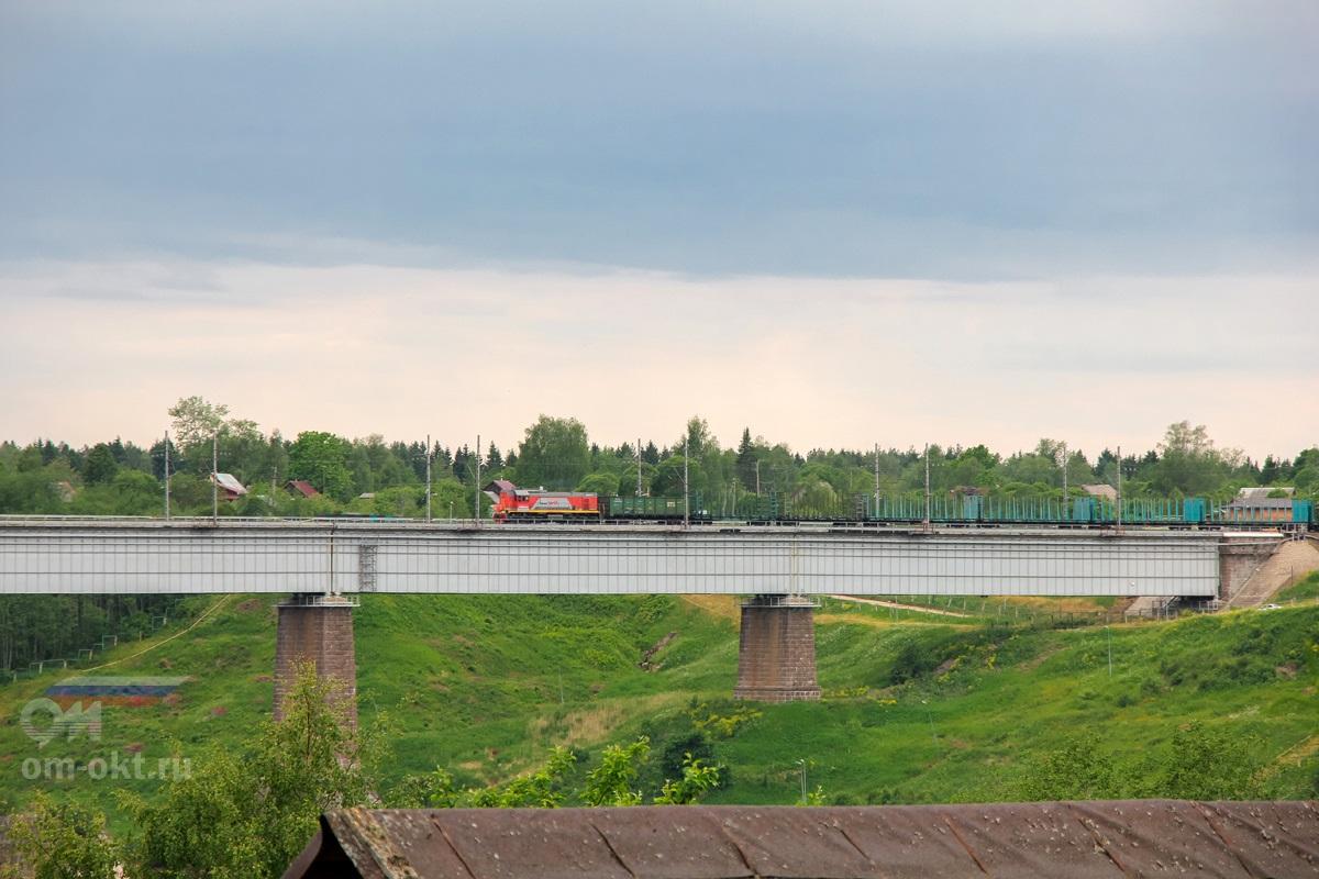 Тепловоз ТЭМ18В с вагонами-лесовозами проследует Мстинский мост