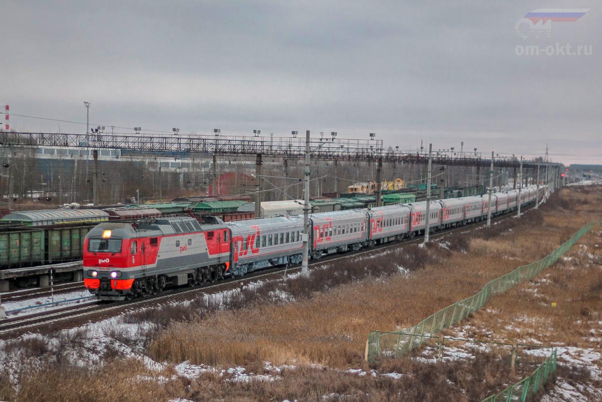 Электровоз ЭП2К-228 в голове пассажирского поезда проследует станцию Тосно